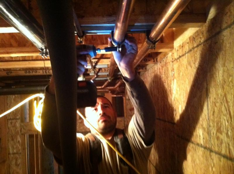 Adrian is shown installing strut clamps on residential water piping system.